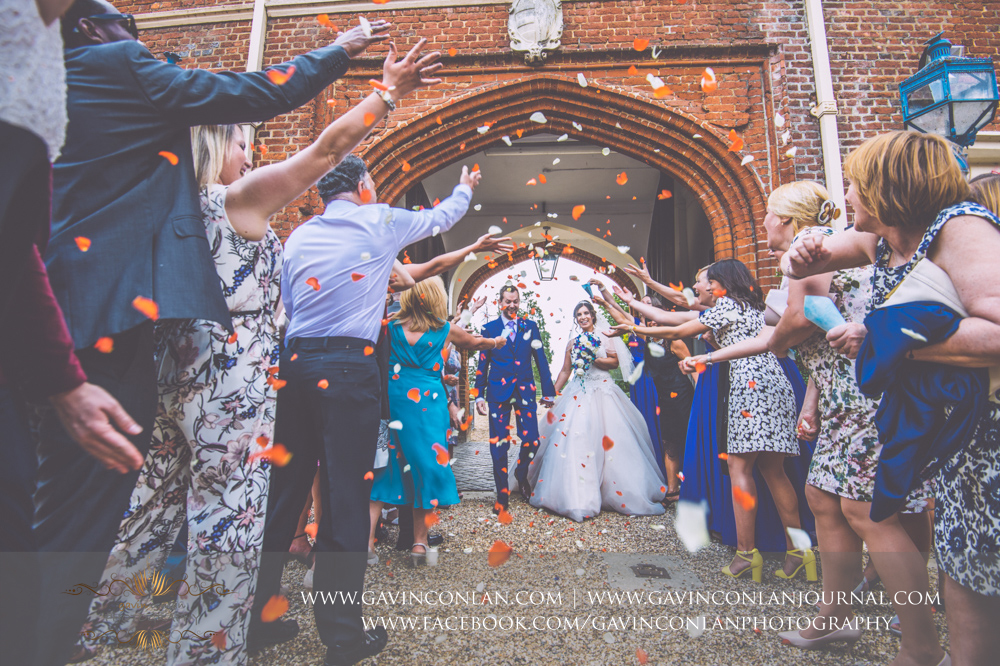 the classic confetti photograph taken in the inner courtyard of Gosfield Hall. Wedding photography at  Gosfield Hall  by Essex wedding photographer  gavin conlan photography Ltd