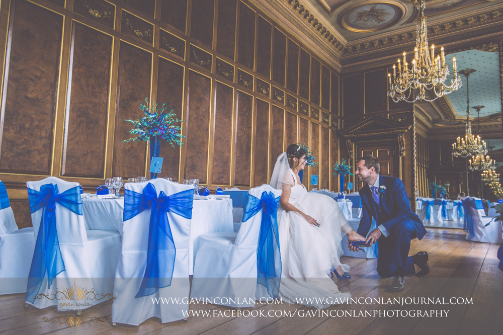 beautiful portrait of the groom on his knee helping his wife put on her blue crystal bridal shoe in the Ballroom. Wedding photography at  Gosfield Hall  by Essex wedding photographer  gavin conlan photography Ltd