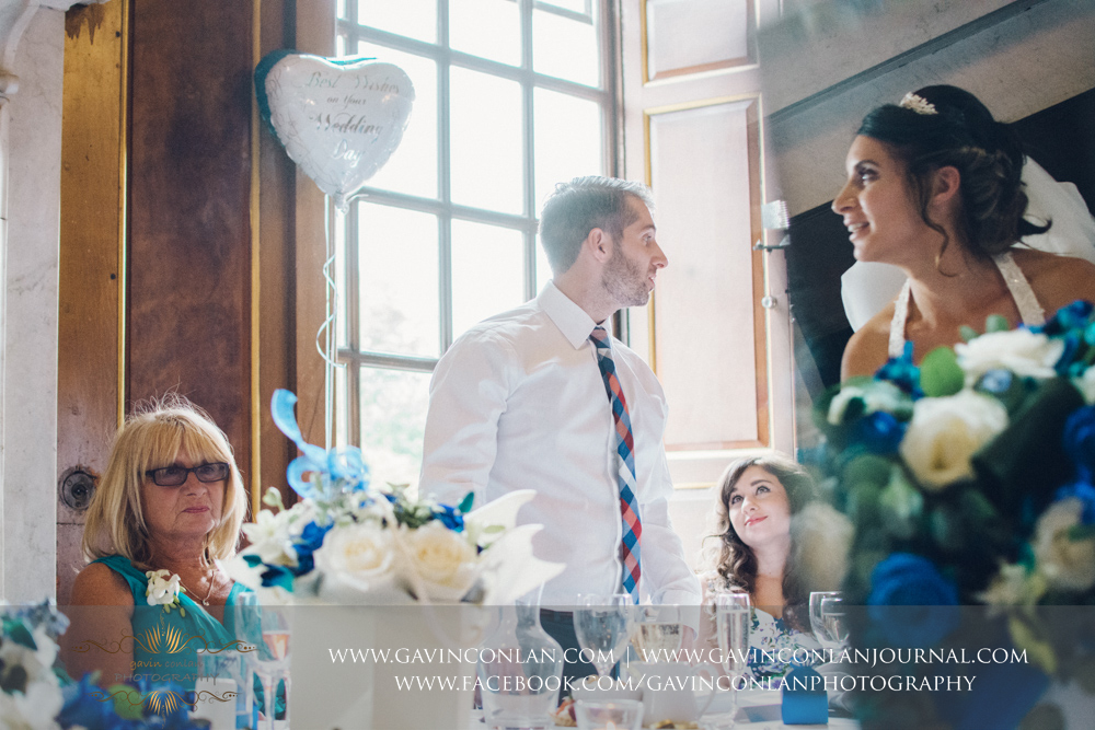 creative portrait of the bride's brother during his wedding breakfast speech with the bride appearing in the reflection, a single frame no photoshop. Wedding photography at  Gosfield Hall  by Essex wedding photographer  gavin conlan photography Ltd