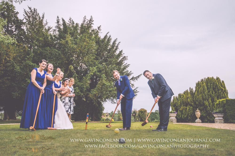 fun portrait of the groom and his best man playing croquet on the lawn outside the main entrance of Gosfield Hall with girls cheering them on in the background. Wedding photography at  Gosfield Hall  by Essex wedding photographer  gavin conlan photography Ltd