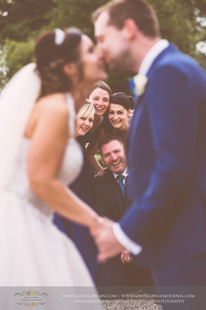 fun and creative portrait of the bridesmaids and best man looking at the camera with the bride and groom sharing a kiss in the foreground. Wedding photography at  Gosfield Hall  by Essex wedding photographer  gavin conlan photography Ltd