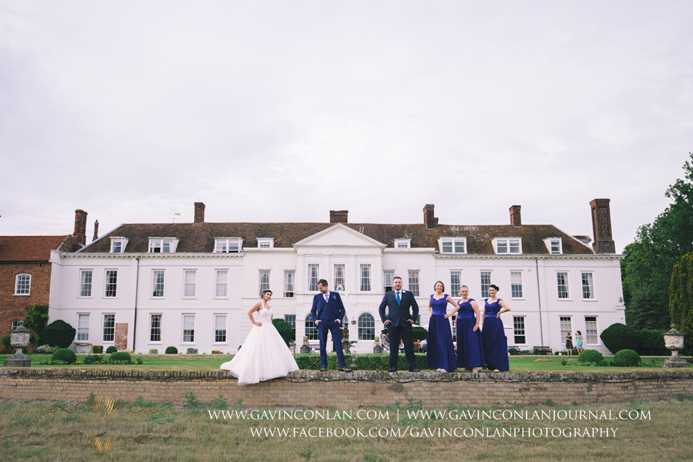 creative fashion portrait of the bride, groom, best man and bridesmaid posing in front of the fountain in the grounds of Gosfield Hall. Wedding photography at  Gosfield Hall  by Essex wedding photographer  gavin conlan photography Ltd