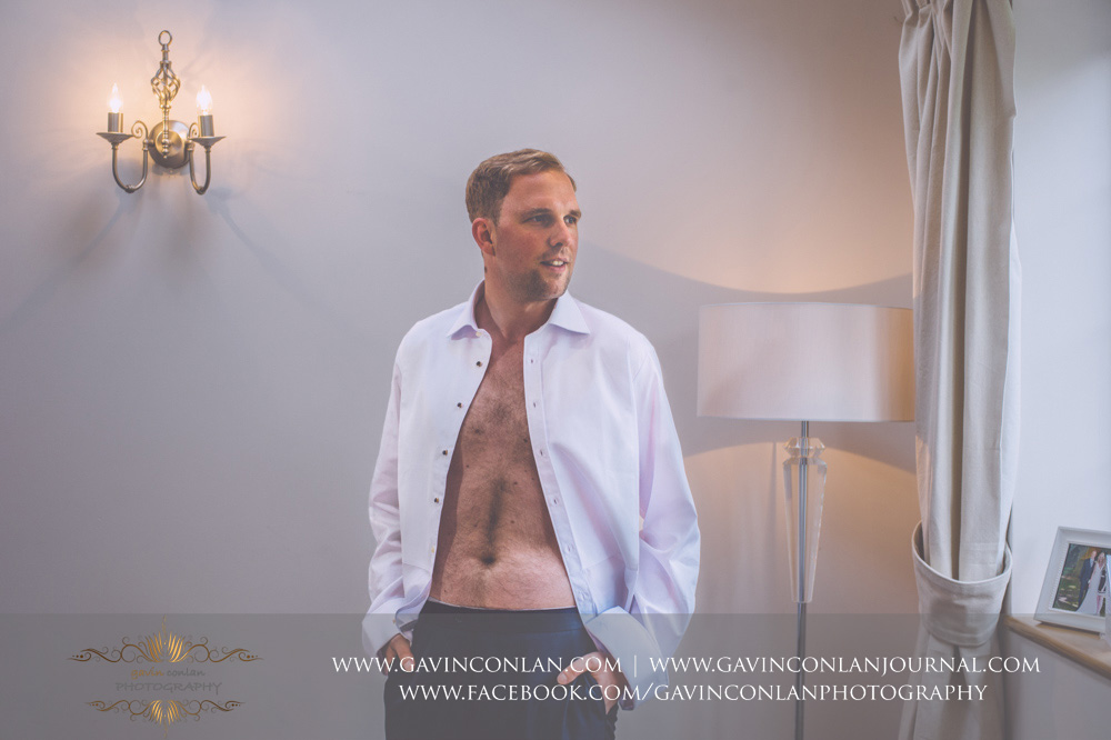 creative portrait of the groom with his shirt open as his about to get dressed. Essex Wedding Photography by  gavin conlan photography Ltd