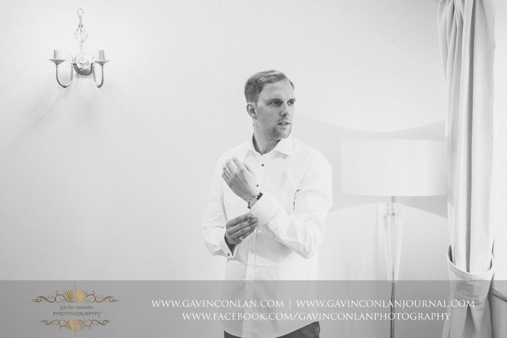 black and white creative portrait of the groom putting on his cuff links as he gets dressed. Essex Wedding Photography by  gavin conlan photography Ltd