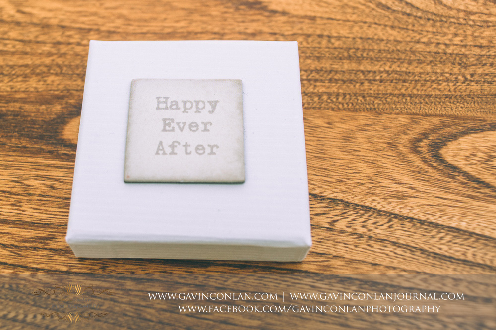 creative detail shot of the sixpence box focussing on the words Happy Ever After which are written on the lid of the box. Essex Wedding Photography by  gavin conlan photography Ltd