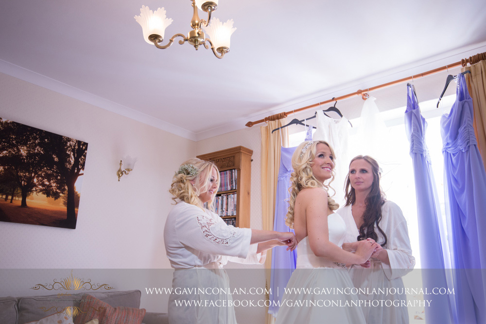 creative portrait of the brides sisters her into her wedding dress. Essex Wedding Photography by  gavin conlan photography Ltd