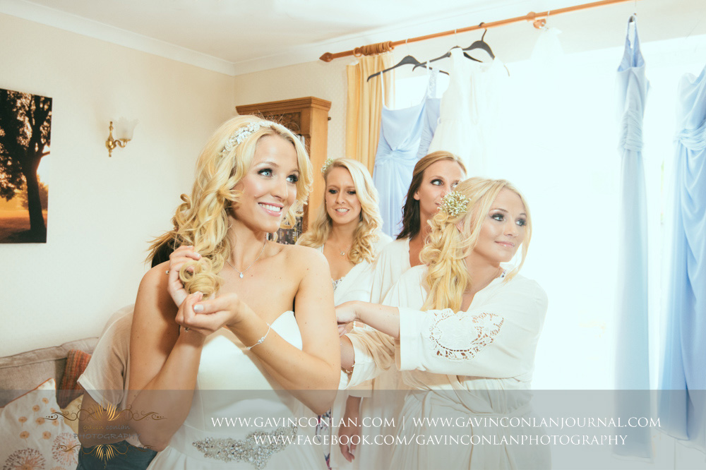beautiful portrait of the bride getting ready with the help of her bridesmaids. Essex Wedding Photography by  gavin conlan photography Ltd