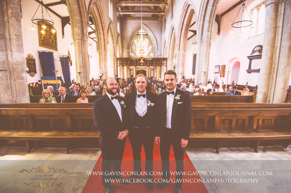 creative portrait of the groom and his best men at the front of the aisle with the guests in the background at St Mary the Virgin Church.  Essex wedding photography at  St Mary the Virgin Church  by  gavin conlan photography Ltd