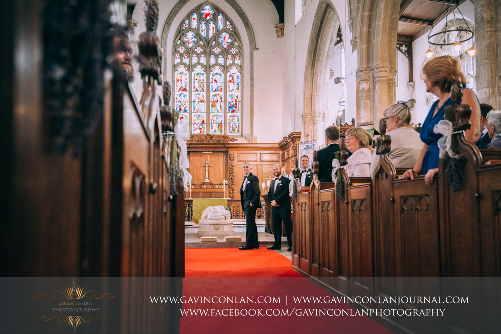 beautiful portrait of the groom looking back down the aisle trying to have a sneak peak of his bride as she walks down the aisle with her father at St Mary the Virgin Church.  Essex wedding photography at  St Mary the Virgin Church  by  gavin conlan photography Ltd
