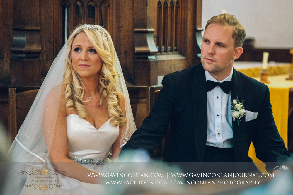 beautiful portrait of the bride and groom sitting down holding hands during the wedding ceremony at St Mary the Virgin Church.  Essex wedding photography at  St Mary the Virgin Church  by  gavin conlan photography Ltd
