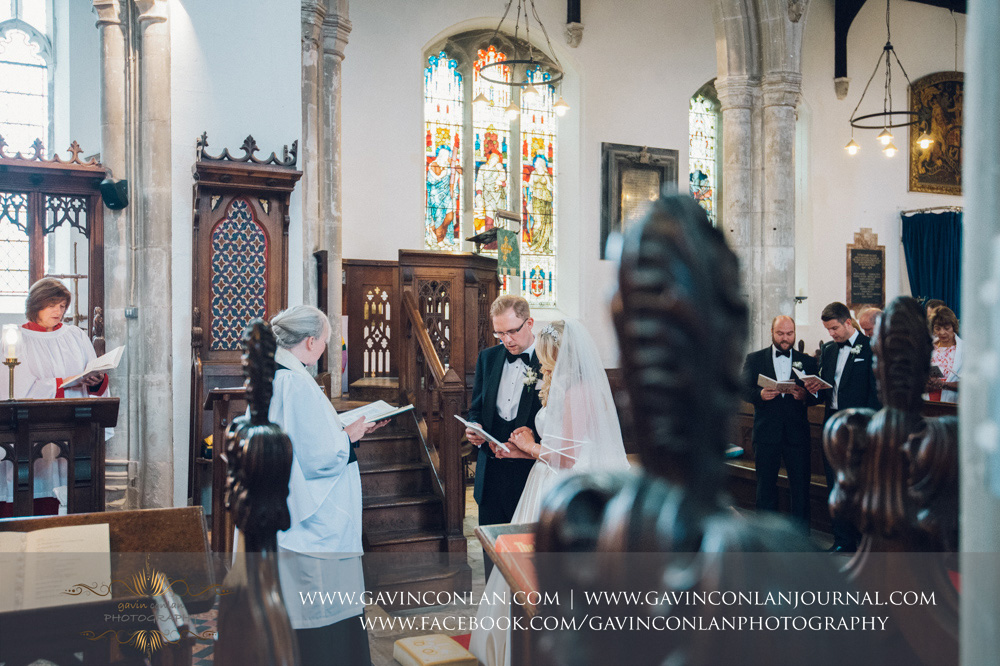 creative ceremony portrait of the bride and groom singing a hymn during the service at St Mary the Virgin Church.  Essex wedding photography at  St Mary the Virgin Church  by  gavin conlan photography Ltd