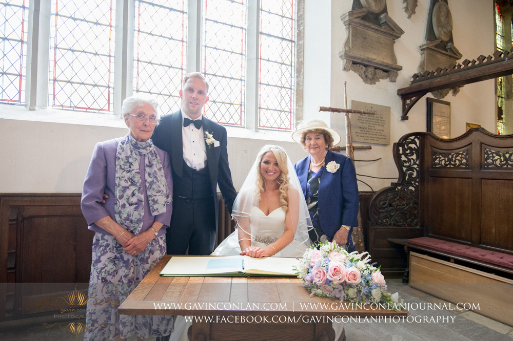 creative portrait of the bride and groom with their two witnesses signing the register at St Mary the Virgin Church.  Essex wedding photography at  St Mary the Virgin Church  by  gavin conlan photography Ltd