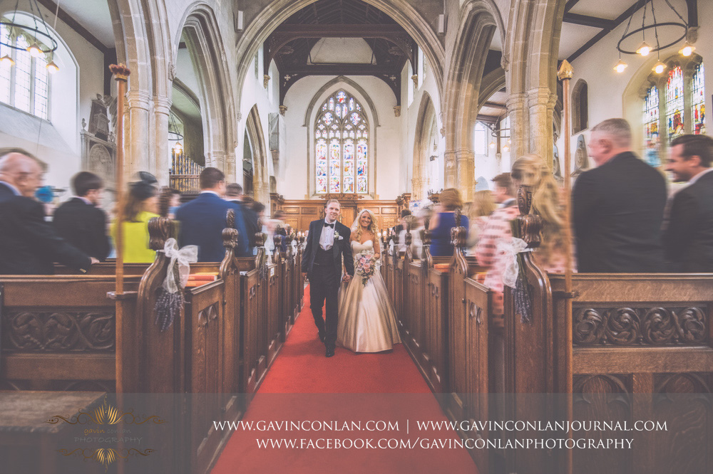 creative portrait of the bride and groom holding hands walking down the aisle as Mr and Mrs at St Mary the Virgin Church.  Essex wedding photography at  St Mary the Virgin Church  by  gavin conlan photography Ltd