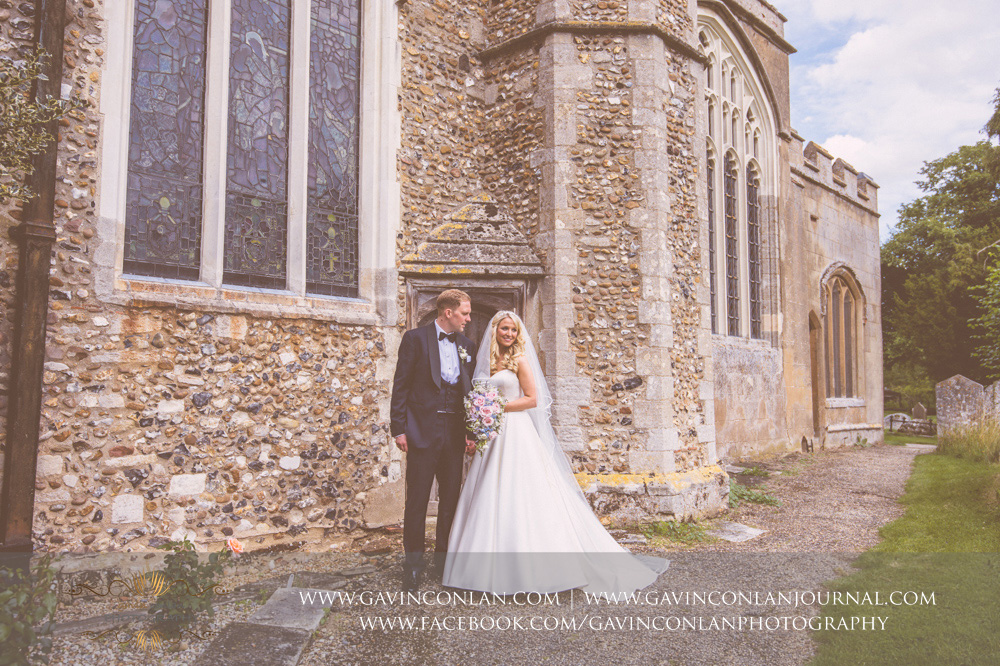 creative portrait of the groom looking at his bride outside St Mary the Virgin Church.  Essex wedding photography at  St Mary the Virgin Church  by  gavin conlan photography Ltd