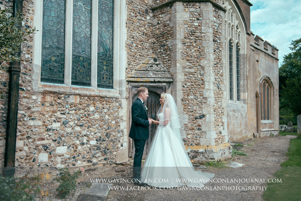 a beautiful creative portrait of the bride and groom holding hands outside St Mary the Virgin Church. Essex wedding photography at  St Mary the Virgin Church  by  gavin conlan photography Ltd