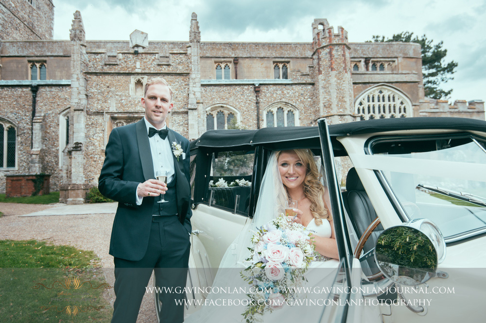 a beautiful portrait of the bride sitting in the front seat of the wedding car with her groom standing next to her outside St Mary the Virgin Church. Essex wedding photography at  St Mary the Virgin Church  by  gavin conlan photography Ltd