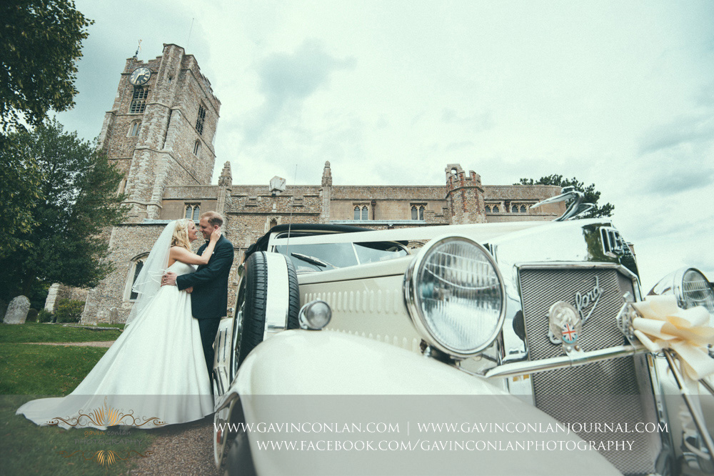 creative portrait of the bride and groom posing next to their wedding car outside St Mary the Virgin Church. Essex wedding photography at  St Mary the Virgin Church  by  gavin conlan photography Ltd