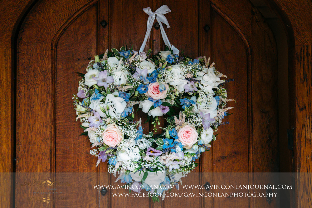 creative detail photograph of the stunning floral reef on the door of the main entrance into Great Hallingbury Manor. Essex wedding photography at  Great Hallingbury Manor  by  gavin conlan photography Ltd