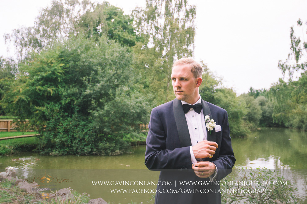 creative james bond style portrait of the groom at Great Hallingbury Manor. Essex wedding photography at  Great Hallingbury Manor  by  gavin conlan photography Ltd