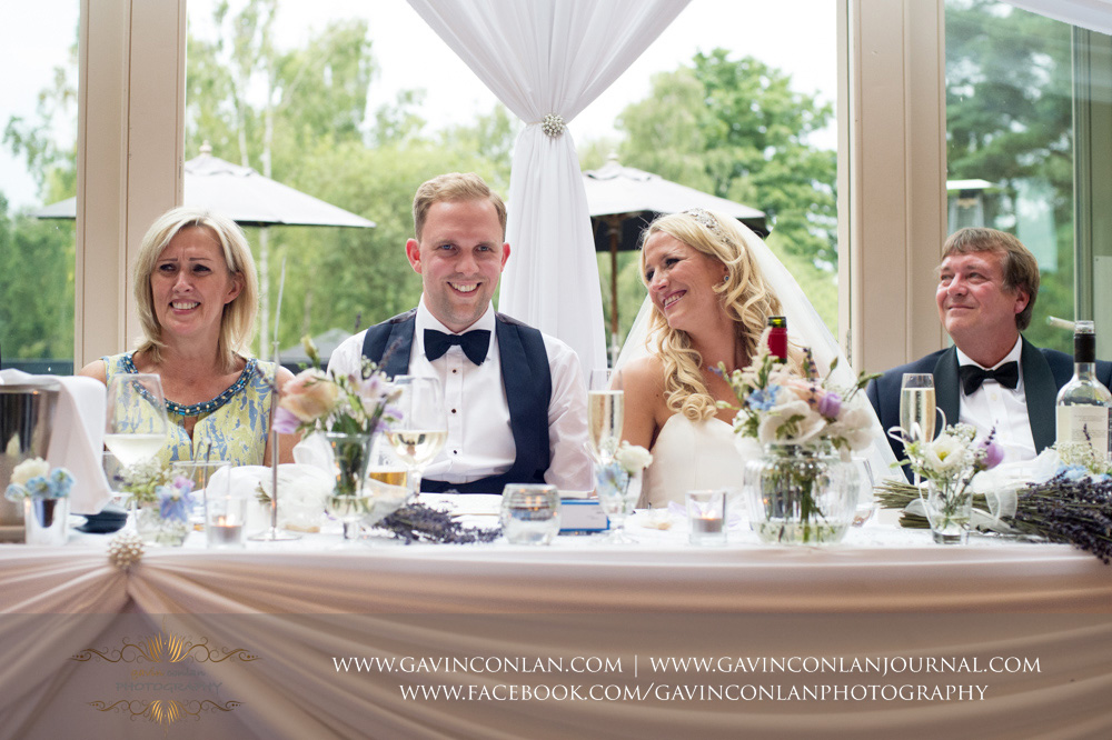 beautiful portrait showcasing beautiful expressions of the bride, groom, grooms mother and brides father during the speeches at Great Hallingbury Manor. Essex wedding photography at  Great Hallingbury Manor  by  gavin conlan photography Ltd