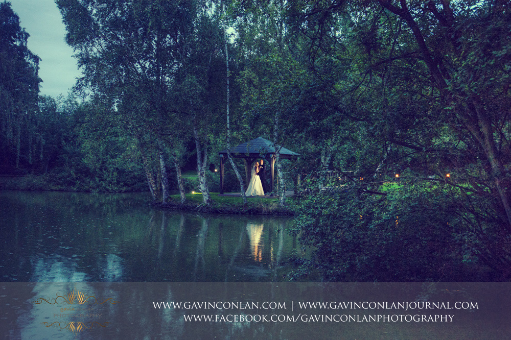 a beautiful portrait of the bride and groom posing by the lake under the gazebo at Great Hallingbury Manor. Essex wedding photography at  Great Hallingbury Manor  by  gavin conlan photography Ltd