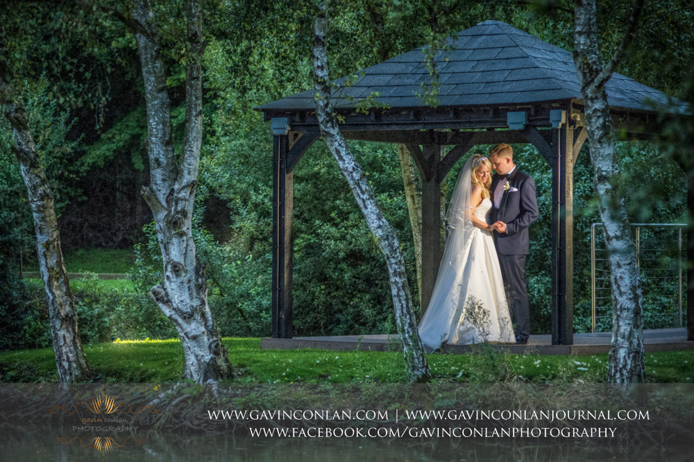 a stunning portrait of the bride and groom posing under the gazebo at Great Hallingbury Manor. Essex wedding photography at  Great Hallingbury Manor  by  gavin conlan photography Ltd