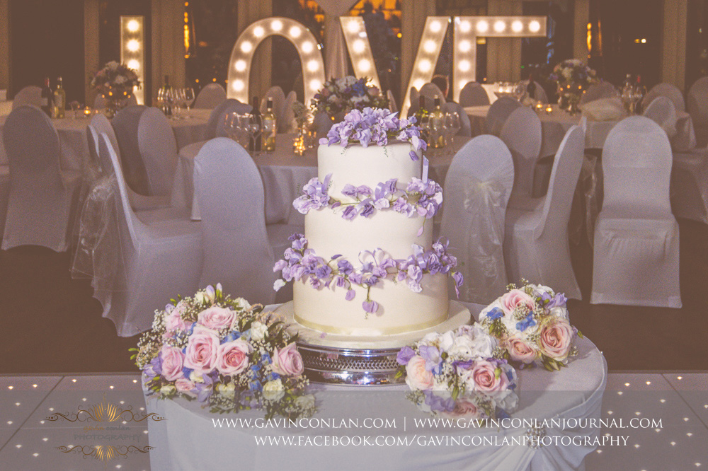 creative detail photograph of their wedding cake on the dane floor with the LOVE sign in the background at Great Hallingbury Manor. Essex wedding photography at  Great Hallingbury Manor  by  gavin conlan photography Ltd