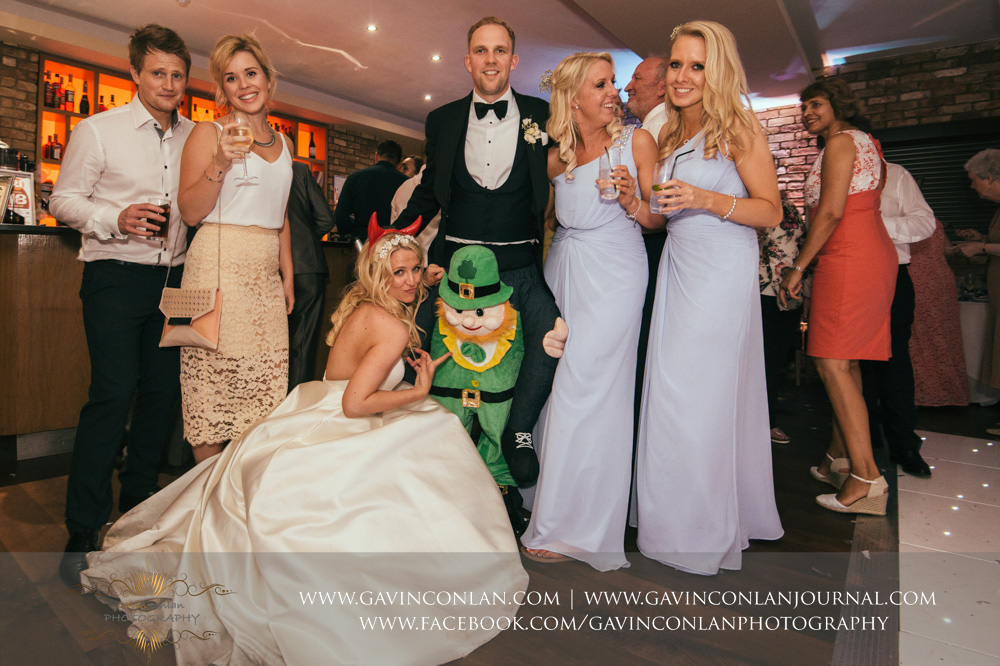 funny portrait of the bride and groom posing with friends and family and their special Irish guest at Great Hallingbury Manor. Essex wedding photography at  Great Hallingbury Manor  by  gavin conlan photography Ltd