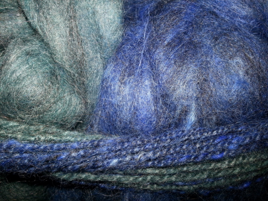Cobalt and teal angora and merino blend. I spun a sample of self-striping yarn which you see around it.