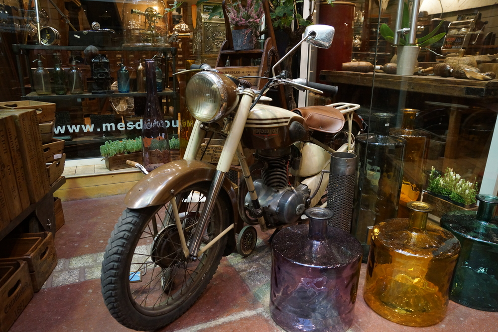 LOVE the juxtaposition of the retro motorbike and amethyst, amber and jade green glass bottles
