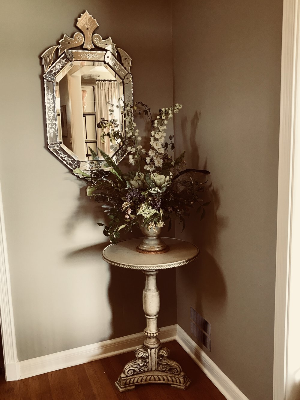 A Venetian mirror and antique Italian table welcome visitors