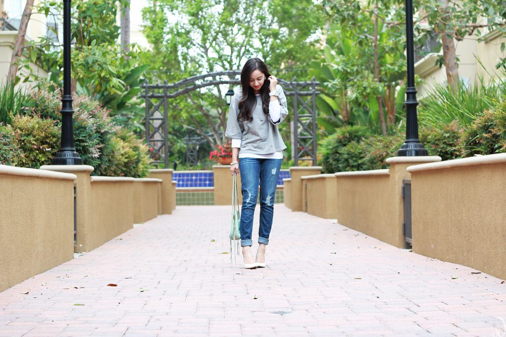 Casual winter layers, embellished sweatshirt, boyfriend jeans, and white pumps