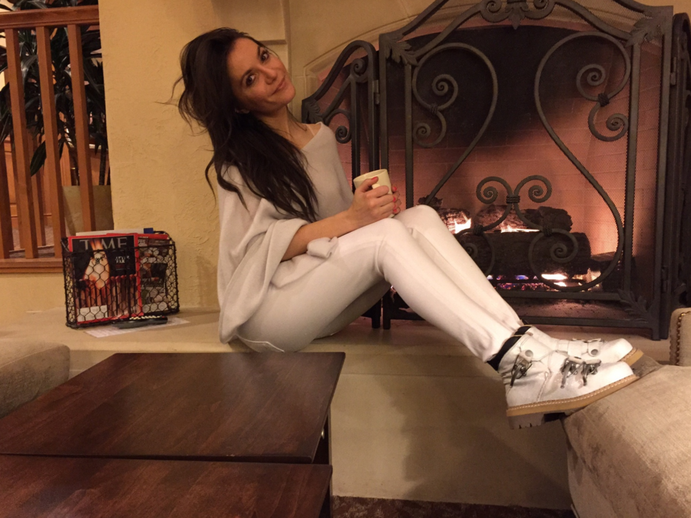 Marina really likes her ski buckle boots, here she is sipping coffee by the fire.