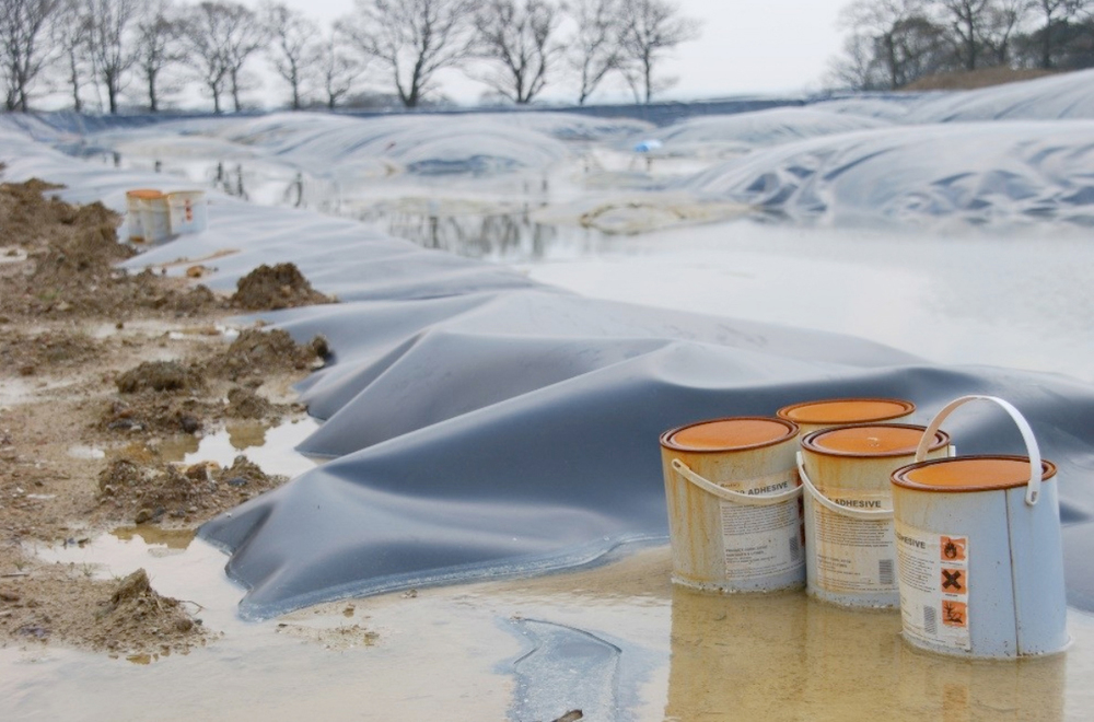 Rusting tins of toxic chemicals next to the lagoon