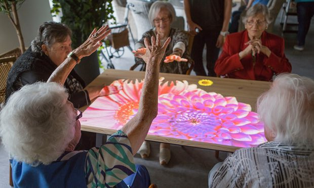 A group of women create a blooming flower on the Tovertafel. Photograph: Job Jansweijer/Tovertafel