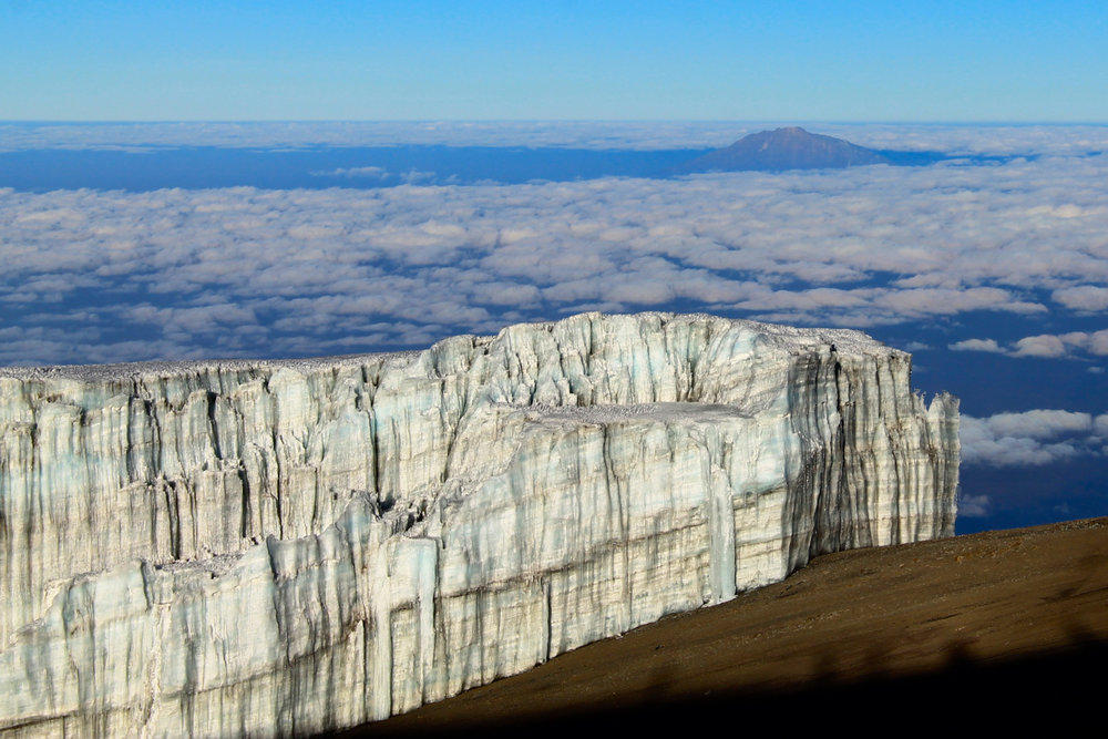 Glacier near the top of Mount Kilimanjaro with Mount Meru across the clouds.