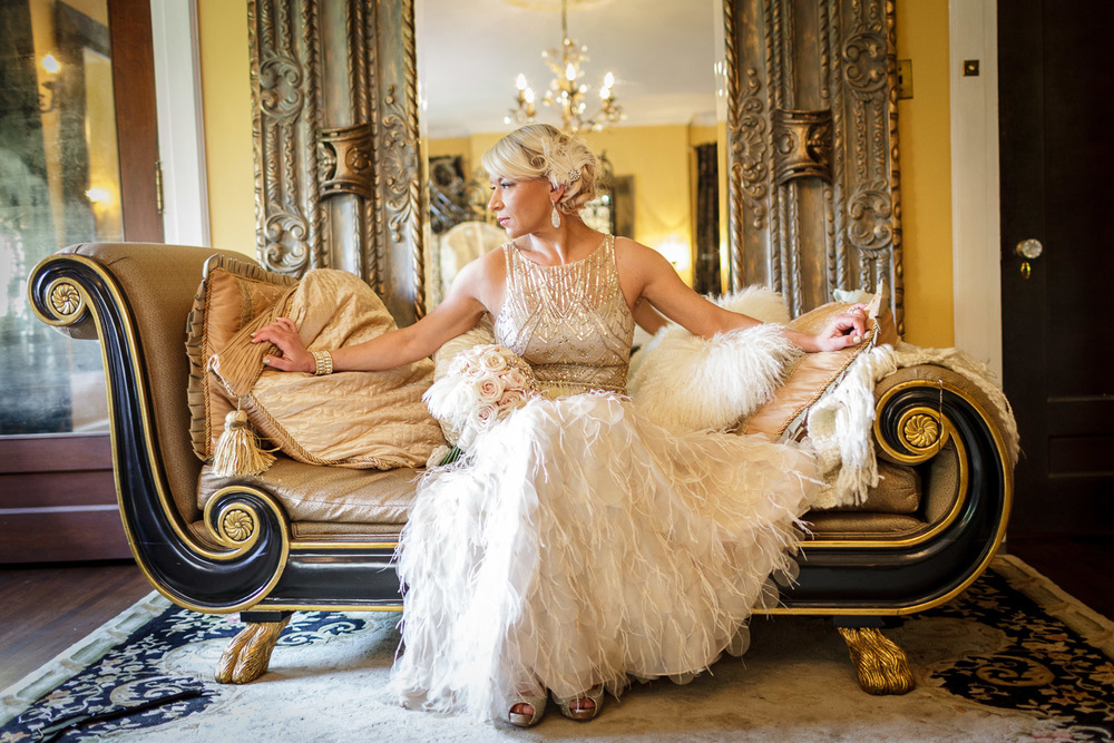 "This is one of those ""I can't believe how great this turned out"" images for me. Marina, the beautiful bride, chose to wear a Gatsby inspired wedding dress adorned with gold and feather like lace reminiscent of the roaring 20's. The bridal suite in the magnificent Henry Hall Wilson House had this beautiful vintage couch along with a gigantic gold trimmed mirror behind it, just begging to be used in a photo. We nabbed this quick bridal portrait just seconds before she walked outside to meet her eagerly awaiting groom Eric."