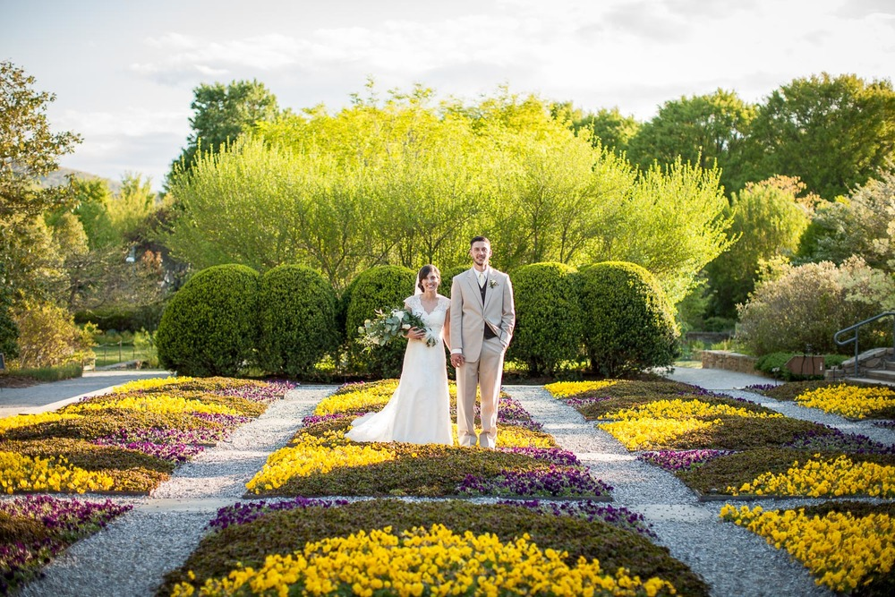 "Another great image from the NC Arboretum, this area is called the ""quilt garden"" and the staff there is constantly changing it depending on the season. The bright colors were perfect for this springtime wedding, and I just love the symmetry of the gardens and the landscaping behind it. My wife always says that the bride and groom Monique and Robby look like cake toppers, and I can't say that I disagree!"