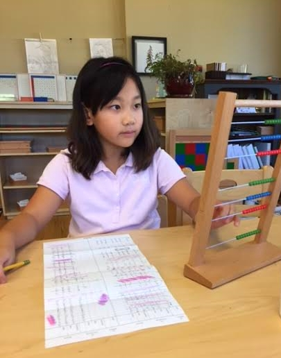 A student working on subtraction dynamic (carrying over) work by using the large bead frame