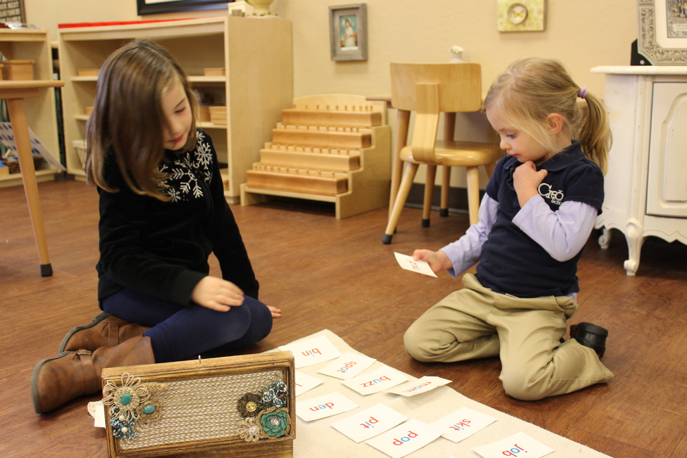 A child helping a younger friend with blending and phonetic reading