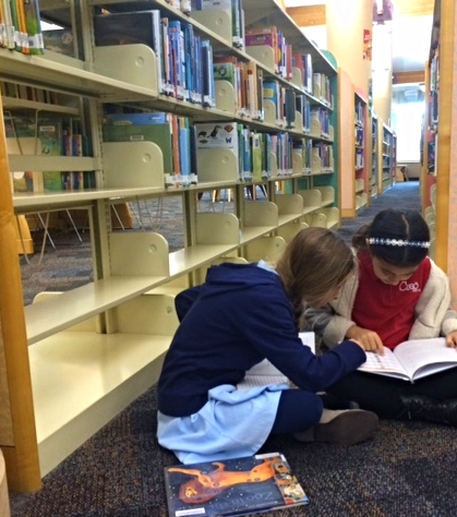 At the Library; these two friends making sure that they have accurate information in this book for their research work.
