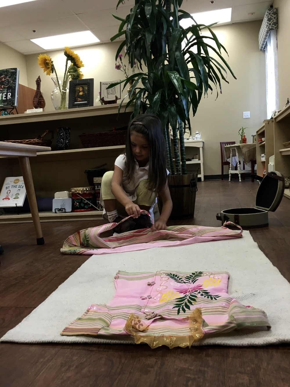 Folding a child's size traditional Indian Sari.