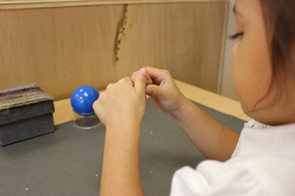 Concentrating on smoothing over the face of the sphere she created with modeling clay.
