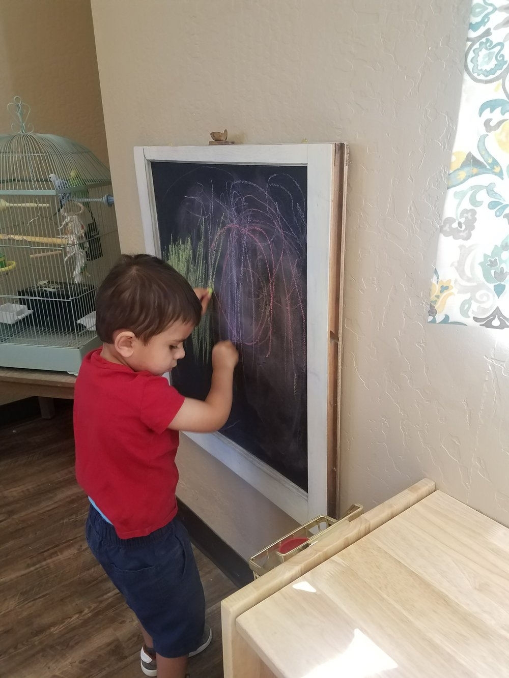 Using the chalk board to freely draw as the development of gross motor skills are supported