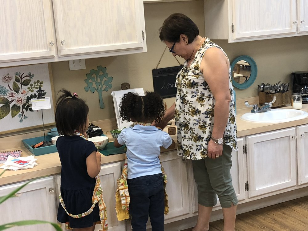 "Assistant directing the children on what foods to get from the refrigerator to prepare snack. ""Trae un pepino"" (bring a cucumber)"