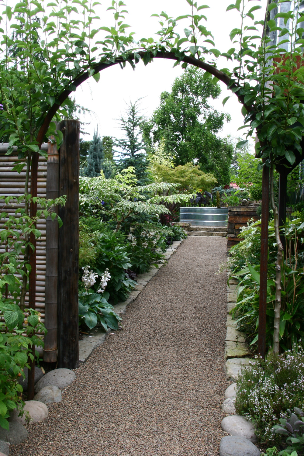 This elegant pea gravel pathway is enhanced and contained by stone borders.