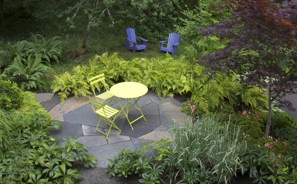 The varied tones of this small, circular Iron Mountain patio create a tapestry-like focal point from the house.