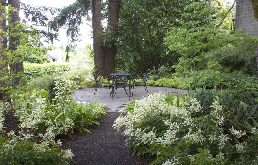 Ample woodland plantings surround an oval-shaped flagstone patio in Eugene, Oregon.
