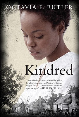 [image description: the book cover of Kindred. There's a photo of a black woman with short hair in a white shirt with the book title and author name overlaid. At the bottom there are photos of small cabins in which enslaved people lived pre-1860s.]