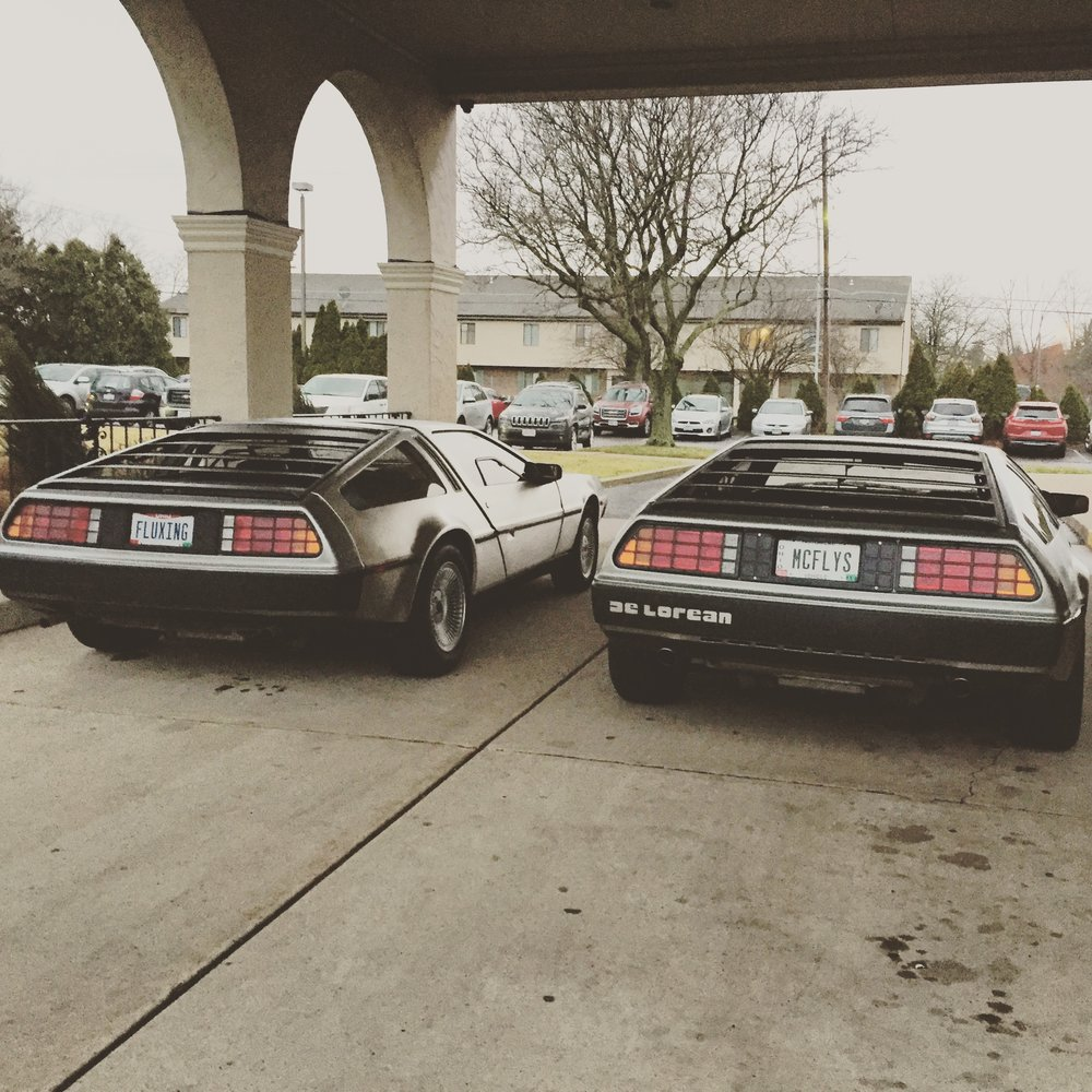 Some fellow DeLorean lovers in town brought their rides out to the book signing! [image description: Two DeLorean cars are parked side by side outside the venue where author Ernest Cline was speaking.]